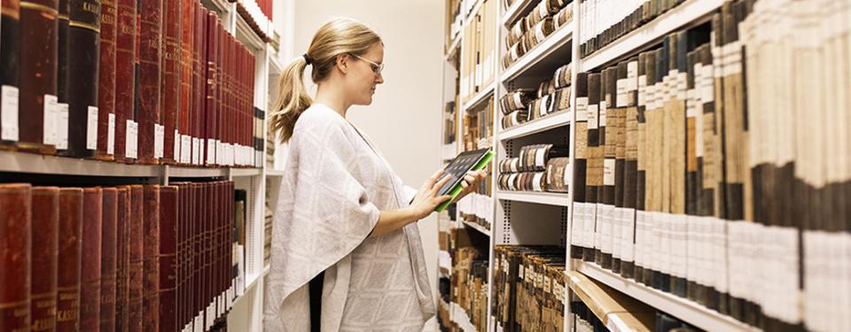 Bilden visar en kvinna i ett arkiv med massor av böcker.