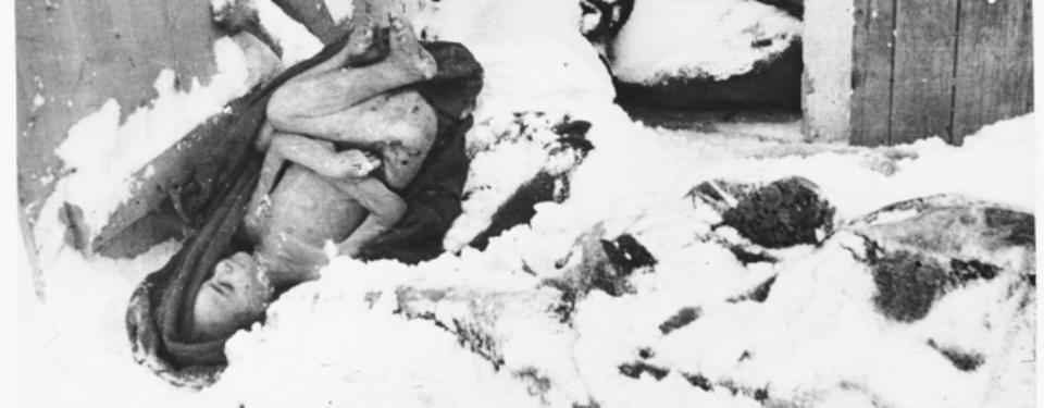 Bilden visar en naken kropp liggandes på en filt i snön, bredvid snöövertäckta filtar.