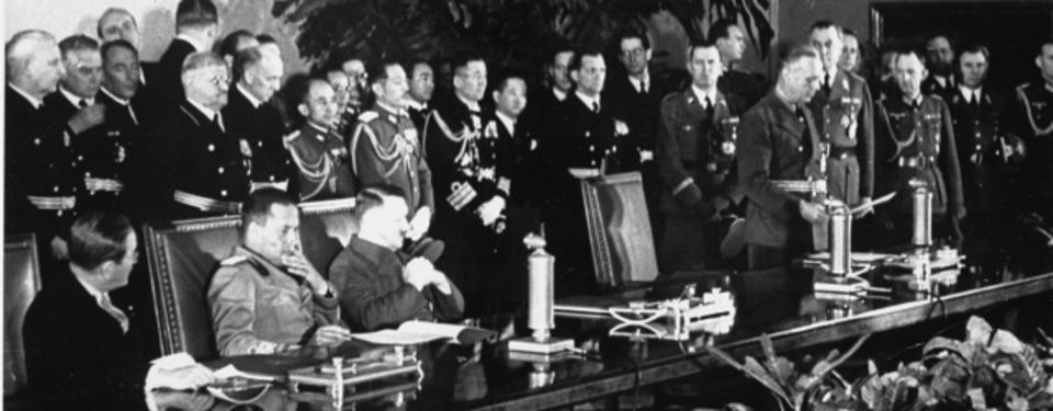Bilden visar tre sittande män vid långt bord, en fjärde man står och läser dokument. Flera kostymklädda, dekorerade män i bakgrunden.