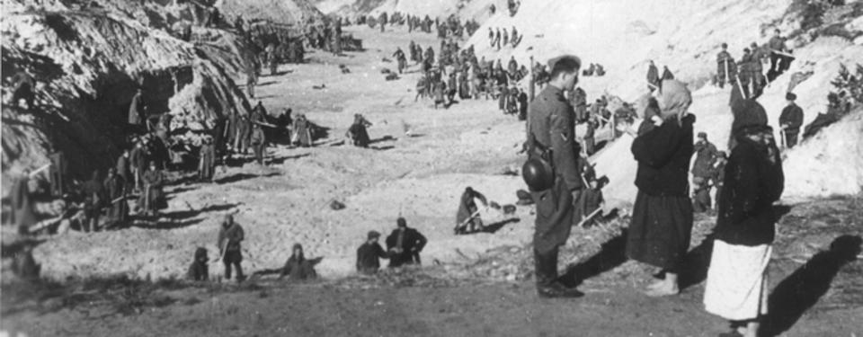 Bilden visar många uniformsklädda män med spadar i en stor ravin.