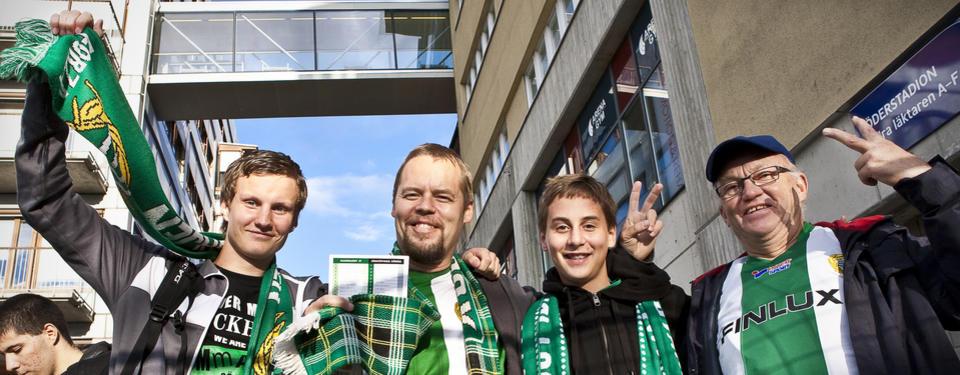 Bilden visar två yngre och två äldre män som håller armarna på varandras axlar och har grön och vita halsdukar och tröja.