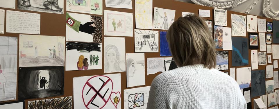 Bilden visar en person som står och tittar på teckningar.