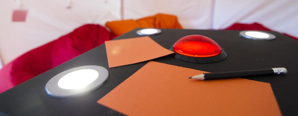 Bild på papper, pennor och ljudknapp inne i tältutställningen
