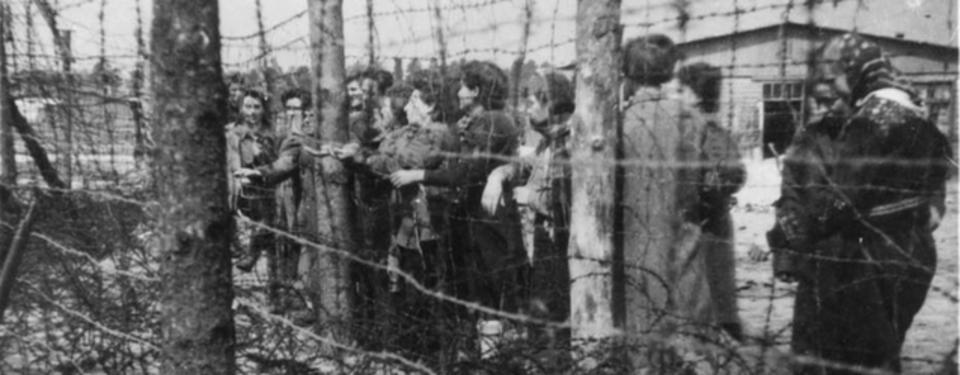 Bilden visar ett femtontal kvinnor ståendes nära taggtrådsstängsel.