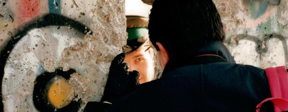 Två personer tittar på varandra genom ett hål i muren.