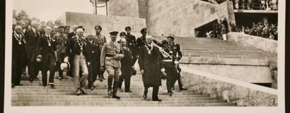 Bilden visar Adolf Hitler omgiven av soldater och välklädda dekorerade civila män gåendes nedför trappa.