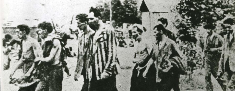 Bilden visar åtta män, gåendes två och två på led.