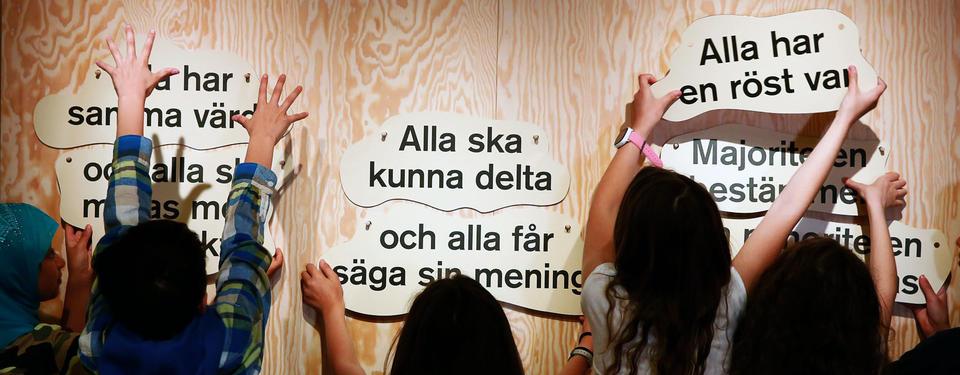 Bilden visar elever som håller i skyltar i utställningen med olika demokratiska budskap som Alla ska kunna delta och alla får säga sin mening.