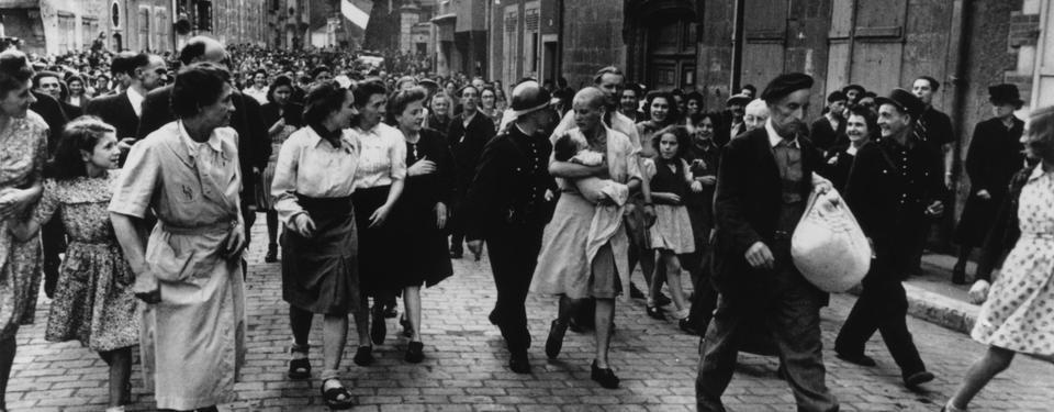 Bilden visar större folkmassa på stadsgata, en soldat går väldigt nära en kvinna med rakat huvud och ett spädbarn i famnen.