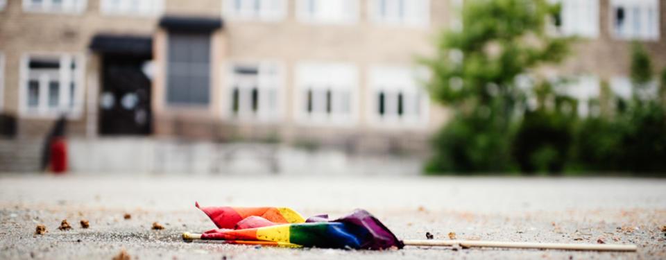 Bilden visar en regnbågsflagga som ligger på en skolgård.