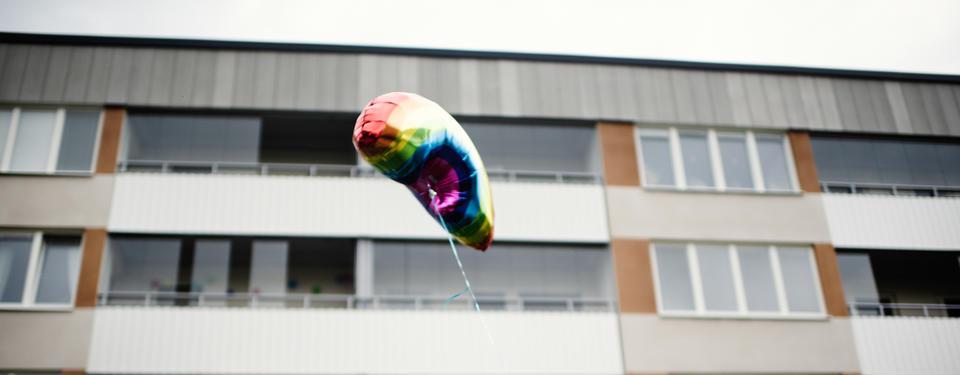 Bilden visar ett bostadshus och en ballong i regnbågsfärger