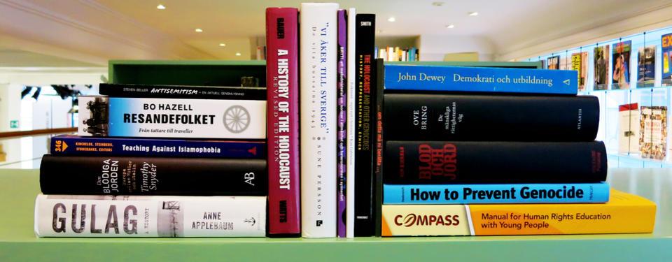 Foto på böcker som ligger på en hylla i biblioteket