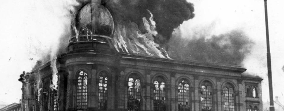 Bilden visar en kyrkobyggnad där eldslågor och rök kommer ut ur fönster och tak.