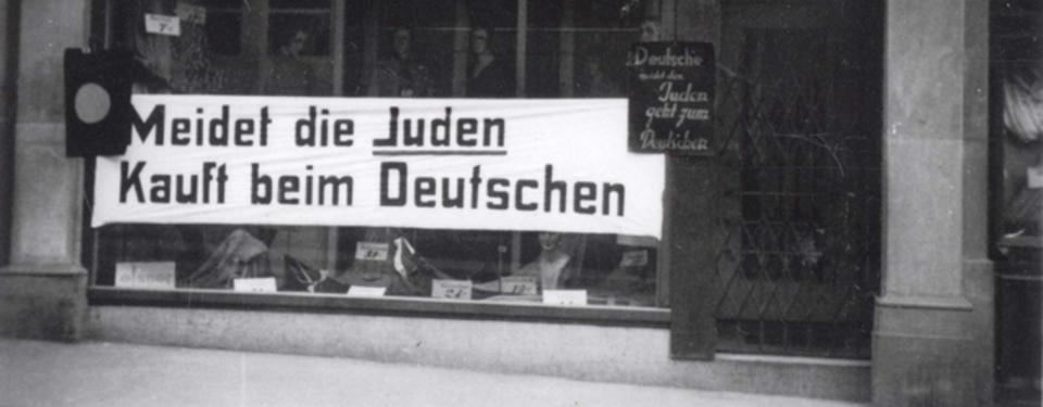 Bilden visar ett butiksfönster till hälften täckt av banderoll med texten: Meidet die Juden Kauft beim Deutschen.
