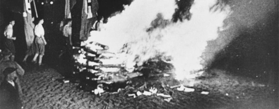 Bilden visar människor som tittar på brinnande hög. Pojkar med svastikafanor i bakgrunden.