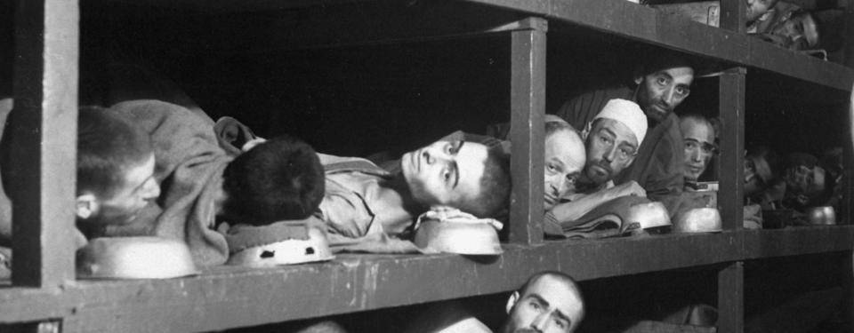 Bilden visar män liggandes i långa våningssängar med skål som huvudkudde.