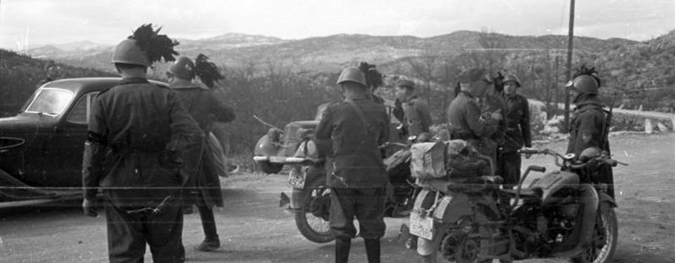 Bilden visar ett tiotal soldater ståendes bland två motorcyklar och två bilar, berg i bakgrunden.