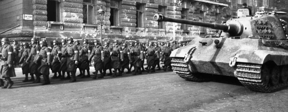 Bilden visar soldater på en gata och en stridsvagn.