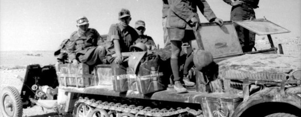 Bilden visar sex soldater ovanpå ett militärfordon.