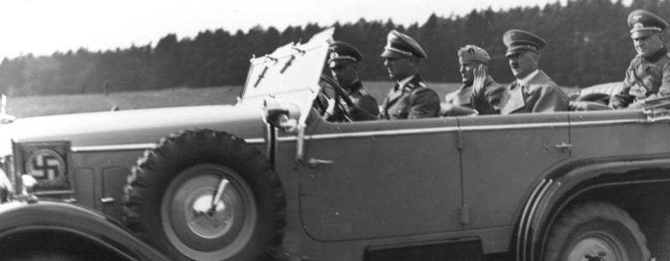 Bilden visar fem män sittandes i öppen bil. Framskärmen dekorerad med en svastika.