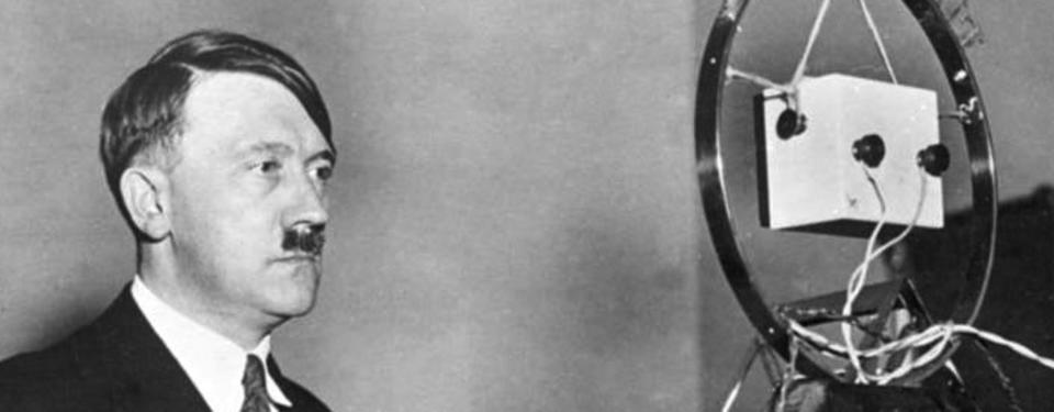 Bilden visar Adolf Hitler framför en mikrofon.