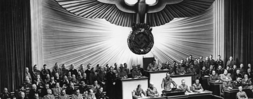 Bilden visar Adolf Hitler ståendes i en talarstol, flera män är bänkade runtomkring honom och i bakgrunden en stor swastika som väggdekoration.