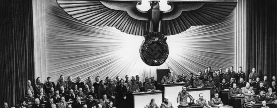 Bilden visar en stor sal med massa människor samlade, ovanför hänger en bild av stor örn.