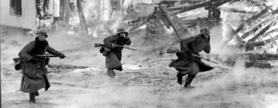 Bilden visar tre soldater vid brinnande byggnader.