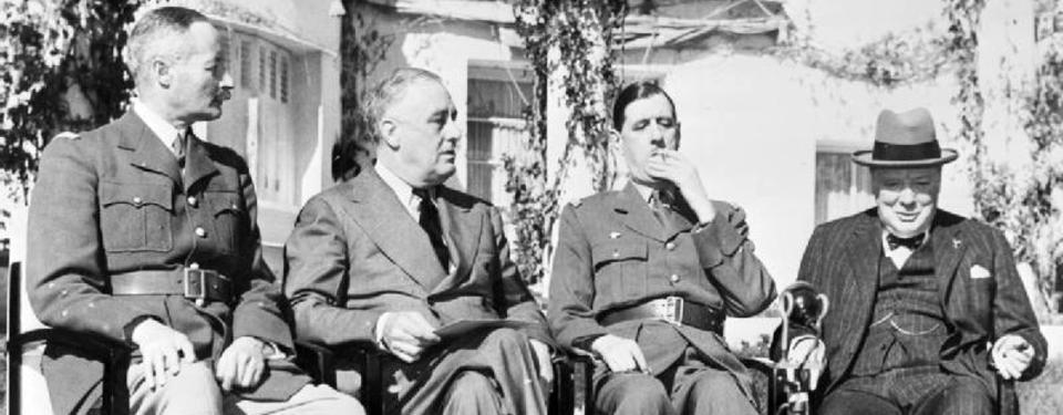 Bilden visar 4 män som sitter uppradade på stolar.