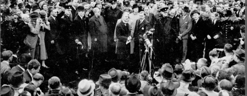 Bilden visar uppställda mikrofoner och stora folkmassor framför och bakom dem.