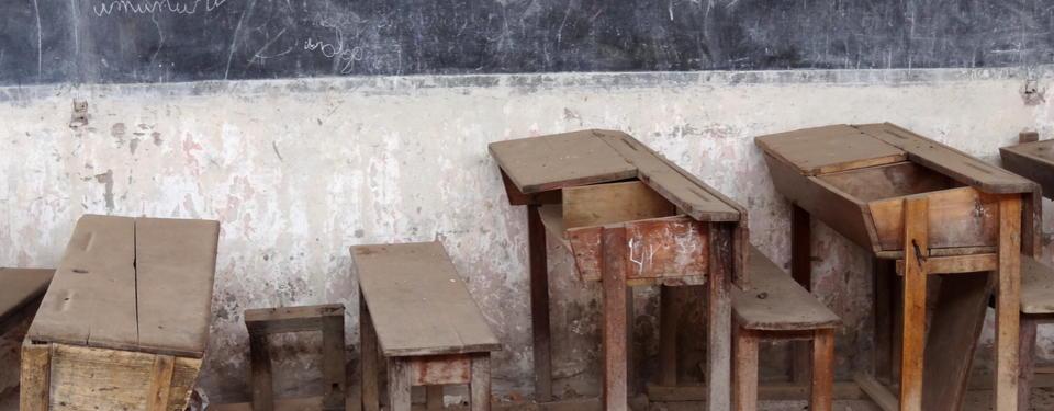 Bilden visar trasiga skolbänkar.