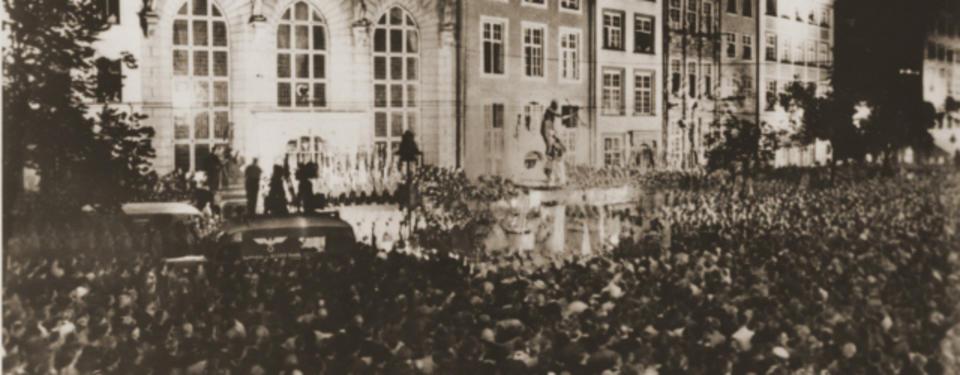 Bilden visar stor, tät folkmassa framför äldre byggnad.