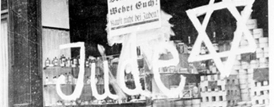 Bilden visar ett skyltfönster med texten jude samt en stjärna skrivet stort på fönstret.