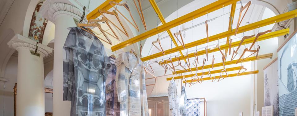 Bilden visar en del av en utställning med galgar i taket.