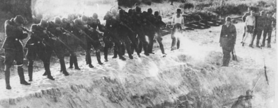 Bilden visar tolv soldater bredvid varandra med höjda gevär, siktandes ned mot grop.