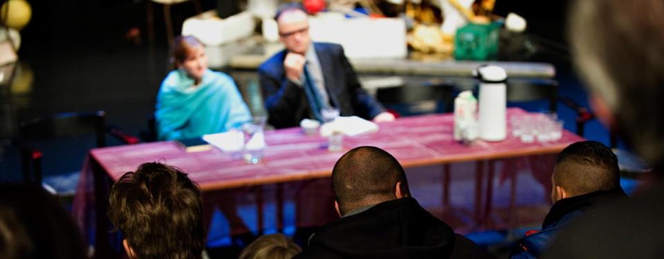 Bilden visar pristagaren sittandes vid ett bord på en scen tillsammans med en annan person och publik som tittar på dem.