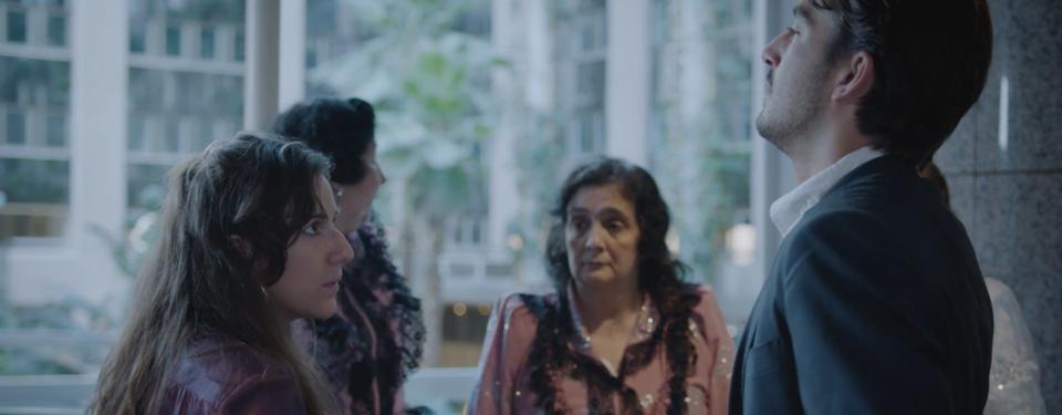 En grupp gäster väntar i lobbyn på ett hotell. Några av kvinnorna bär traditionella romska kläder.