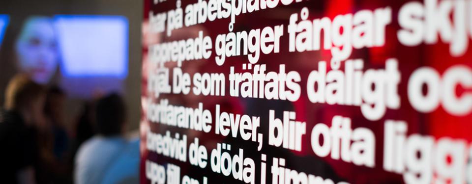 Bilden visar en stor röd plastvägg i utställningen med vit text.