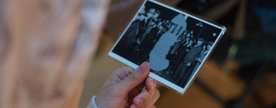 Bilden visar en hand hållandes ett foto på en folksamling ståendes kring ett bortsuddat objekt.