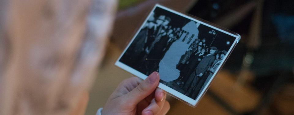 Bilden visar en hand hållandes ett foto med folkmassa kring ett bortsuddat objekt.