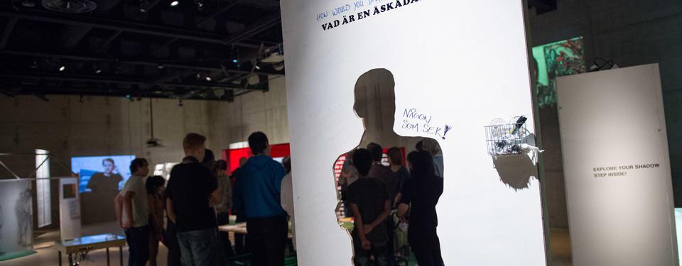 Bilden visar en hög kartongvägg med texten vad är en åskådare och ett utsågat hål i form av en fullstor stående människa och elever runtikring.