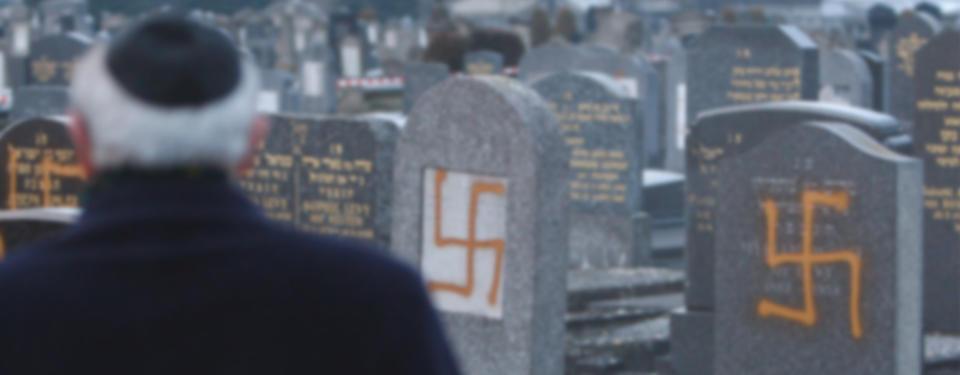 Bilden visar ryggen av en man som står vid en kyrkogård där någon har sprayat hakkors på gravstenar.