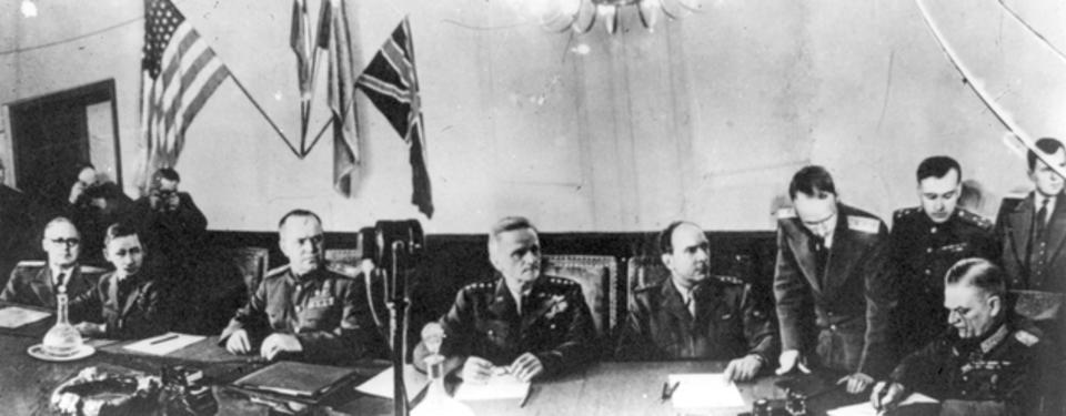 Bilden visar sex män sittandes framför dokument vid avlångt bord.
