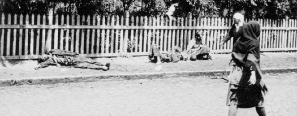 Bild av två avlidna människor på en gata med förbipasserande människor.