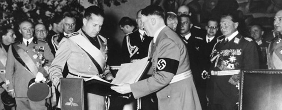 Bilden visar man i tysk uniform som håller fram inbundna dokument för annan uniformsklädd man. Uniformsprydda, dekorerade män i bakgrunden.