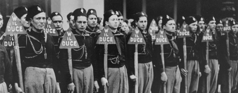 Bilden visar yngre uniformsklädda män på rad i ett par led, hållandes i varsin triangelformad skylt med texten w il duce.