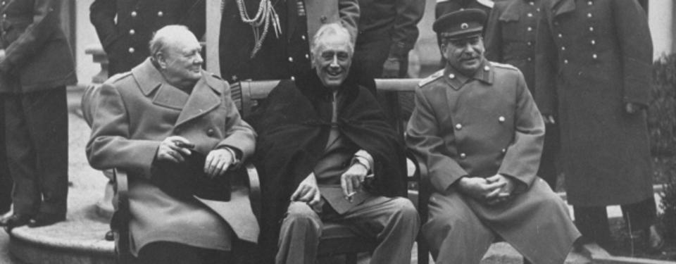 Bilden visar Churchill, Roosevelt och Stalin sittandes framför militärer.
