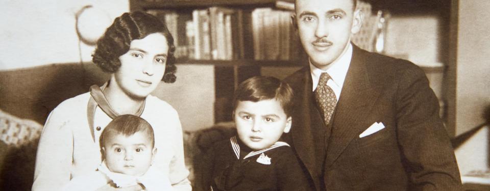 Bilden visar ett gammalt porträtt av en familj med två små barn.