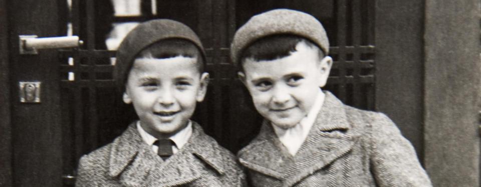 Bilden visar två yngre leende pojkar klädda i ytterplagg med kavajslag och basker.