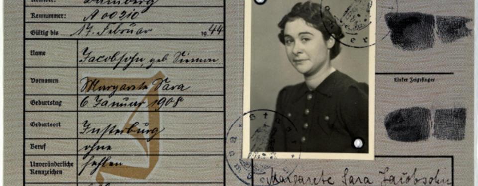 Bilden visar ett pass med ett J över personuppgifterna. Ett porträttfoto och fingeravtryck på andra uppslaget.